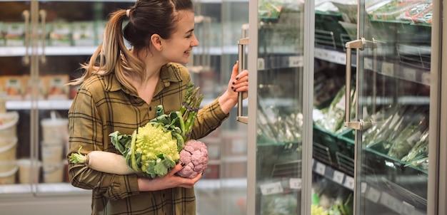 スーパーマーケットの女性。美しい若い女性は新鮮な有機野菜を手で保持し、スーパーで冷蔵庫を開きます