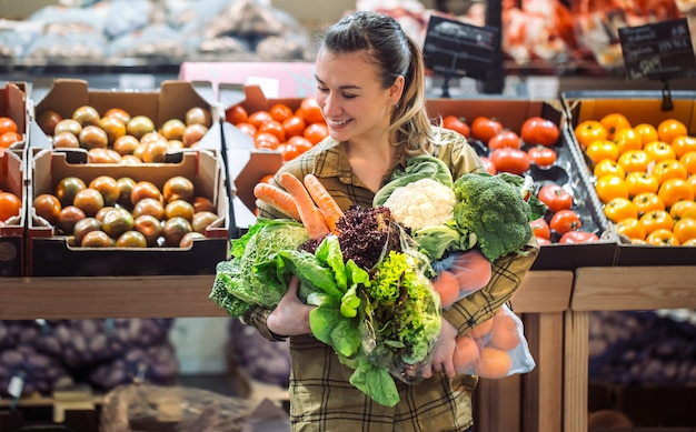 スーパーマーケットの女性。スーパーで買い物や新鮮な有機野菜を買うの美しい若い女性