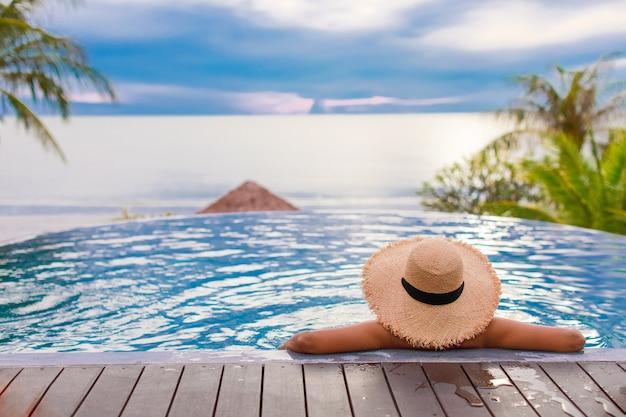 Женщина в плавательных бассейнах в летней шляпе смотрит на море с голубым небом.