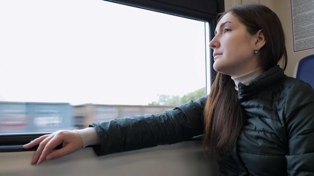 그녀가 앉아서 창 밖을 내다보고 기차에 여자