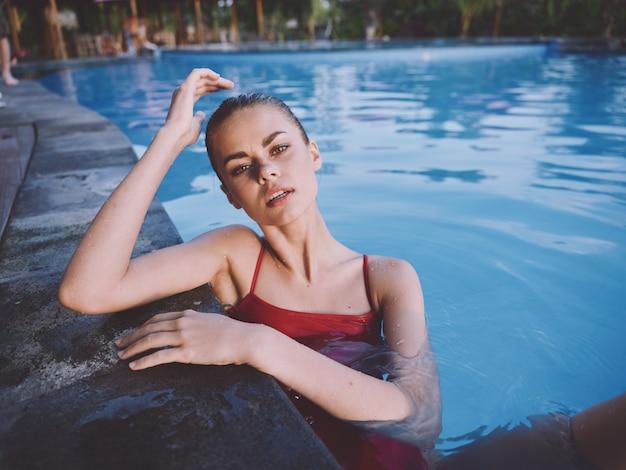 Женщина в прозрачной воде бассейна оперлась локтями о серую плитку расслабиться отдыхать пейзаж