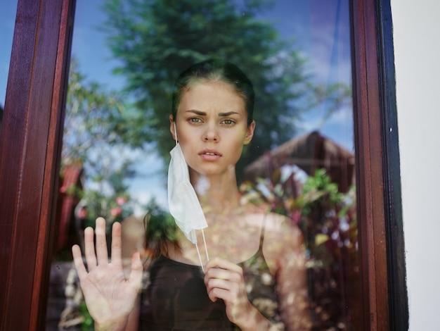 医療用マスクを身に着けている窓の女性悲しげな表情