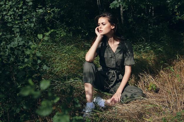 잔디 나머지 신선한 공기 측면보기에 앉아 숲에서 여자