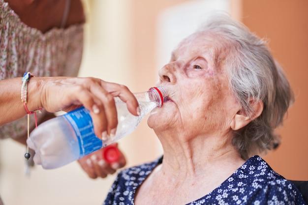 Женщина в свои девяностые пьет воду благодаря другому человеку