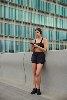 トップショーツとスニーカーの女性がトレーニング中に聴く曲を選ぶ携帯電話が建物の近くの外に立っている耳にワイヤレスヘッドホンを装着している