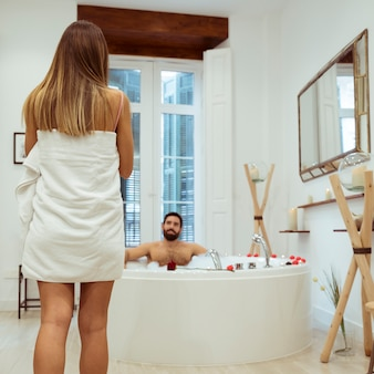 Woman in towel and man in spa tub with foam
