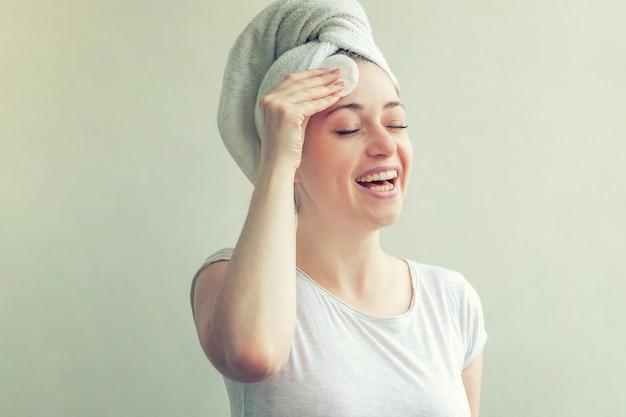 白い背景の上の綿のパッドでメイクを削除する頭の上のタオルの女性