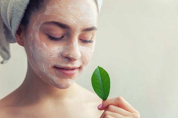 흰색 영양 마스크 또는 얼굴에 크림과 손에 녹색 잎 머리에 수건에 여자, 고립 된 흰색 배경