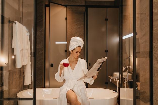 그녀의 머리와 목욕 가운에 수건을 입은 여성이 최신 뉴스를 읽습니다. 욕실에서 포즈를 취하는 차 한잔과 함께 아가씨.