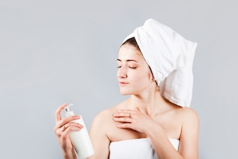 Woman in towels holding cosmetic bottle
