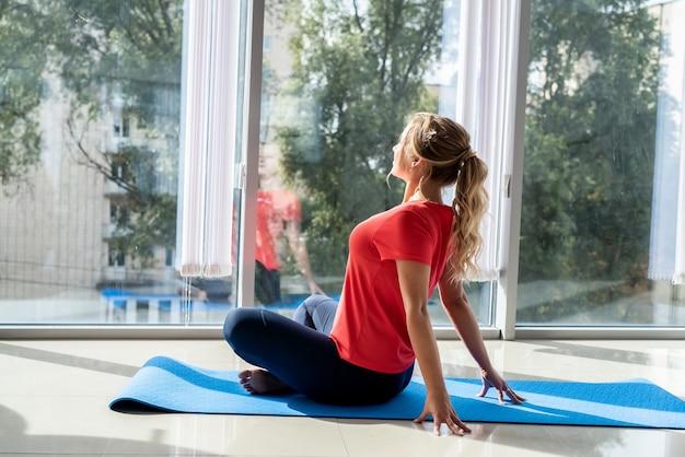 腰痛、リハビリテーションフィットネスからの運動をしているトラックスーツの女性。ヘルスケアの概念