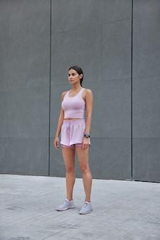 空白の灰色の壁に対してトラックスーツのポーズをとっている女性は、屋外のパーソナルトレーニングプログラムの演習に従ってトレーニングセッションを持っています