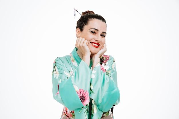 白のあごに拳を持って幸せで陽気な日本の伝統的な着物の女性