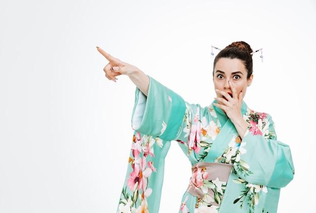 白の何かに人差し指で指している手で口をコーニングショックを受けている伝統的な日本の着物の女性