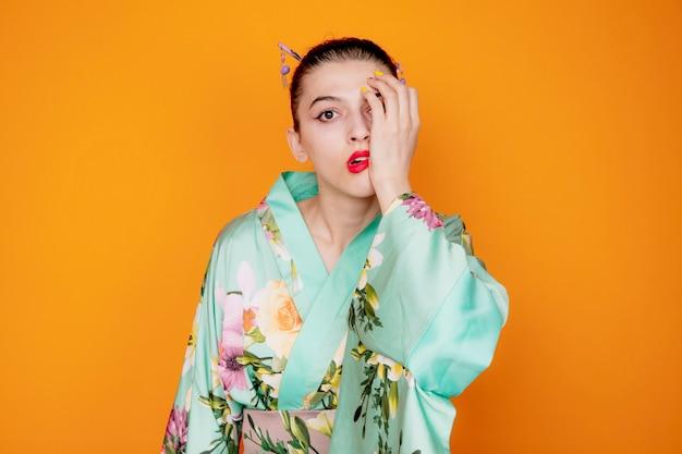 일본 전통 기모노를 입은 여성이 오렌지에 손을 얹고 한쪽 눈을 감고 충격을 받고 있다