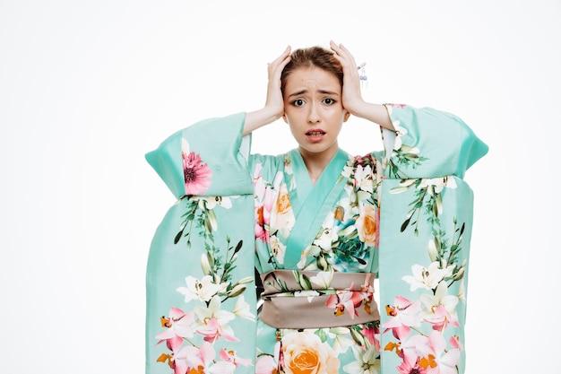 伝統的な日本の着物の女性は、白で彼女の頭に手をつないで混乱し、失望した
