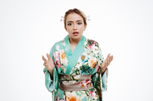 일본 전통 기모노를 입은 여성이 흰색 바탕에 분노와 불만으로 팔을 들고 혼란스럽고 불쾌하다