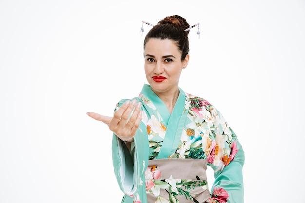 Женщина в традиционном японском кимоно счастлива и позитивна, делая жест рукой на белом