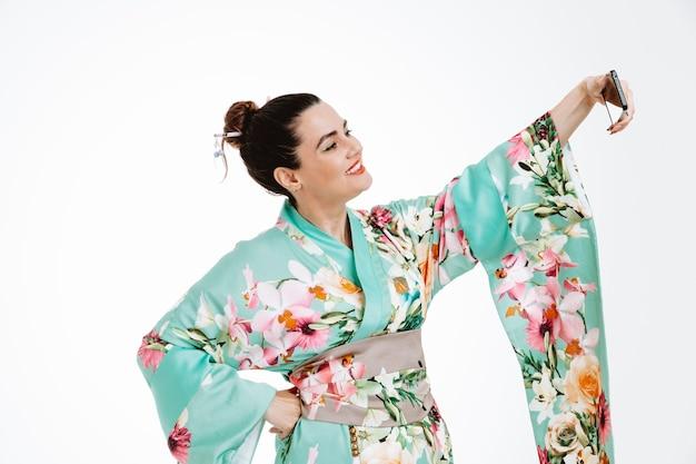 일본 전통 기모노를 입은 여성이 흰색으로 스마트폰을 사용하여 즐겁게 셀카를 하며 행복하고 긍정적인 미소를 짓고 있습니다.