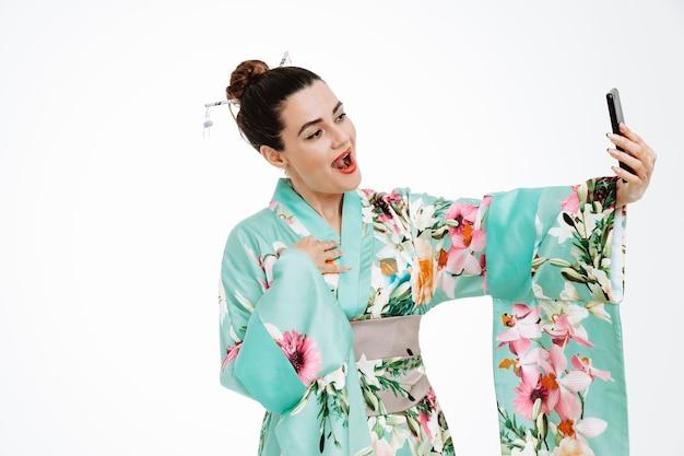 일본 전통 기모노를 입은 여성이 흰색 스마트폰을 사용하여 셀카를 찍으며 행복하고 긍정적인 미소를 짓고 있습니다.
