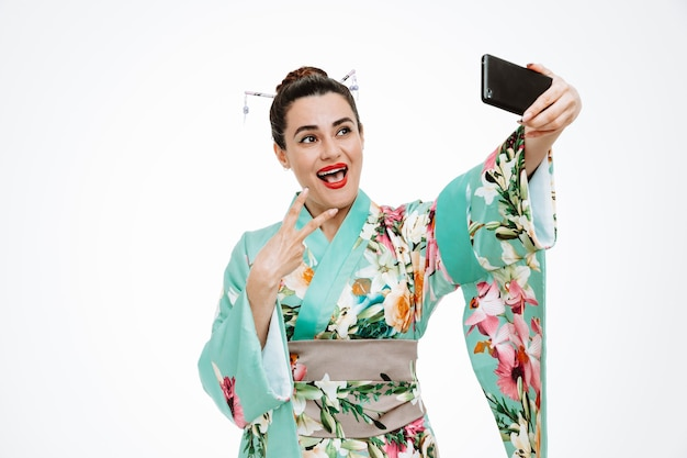 전통적인 일본 기모노를 입은 여성이 흰색으로 스마트폰을 사용하여 셀카를 하고 있는 v-sign을 보여주는 행복하고 긍정적인 미소