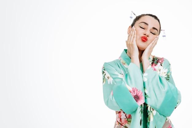일본 전통 기모노를 입은 여성은 눈을 감고 흰색에 키스하는 꿈을 꾸고 행복하고 긍정적입니다.