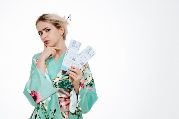 白で彼女のあごに手をつないで懐疑的な表情で航空券を保持している伝統的な日本の着物の女性