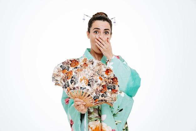 扇子を持っている伝統的な日本の着物の女性は、白の手で口をコーニングショックを受けています