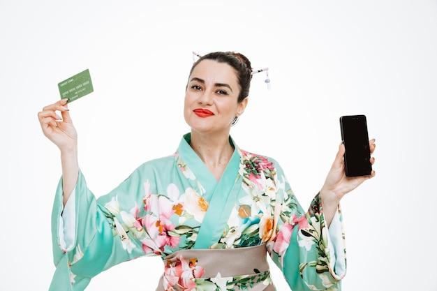 スマートフォンを持っている伝統的な日本の着物の女性は、白で広く笑顔で幸せで喜んでクレジットカードを示しています