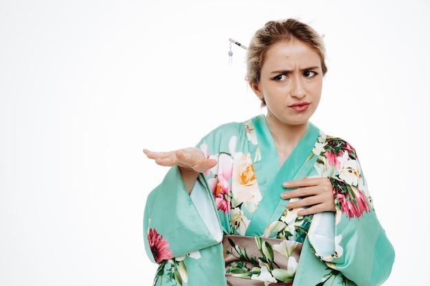 흰색에 손을 올리는 중지 제스처를 만드는 역겨운 표정으로 옆을 바라보는 전통 일본 기모노를 입은 여성