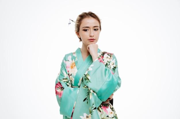 白のあごに手をつないで物思いにふける表情で脇を見る伝統的な日本の着物の女性