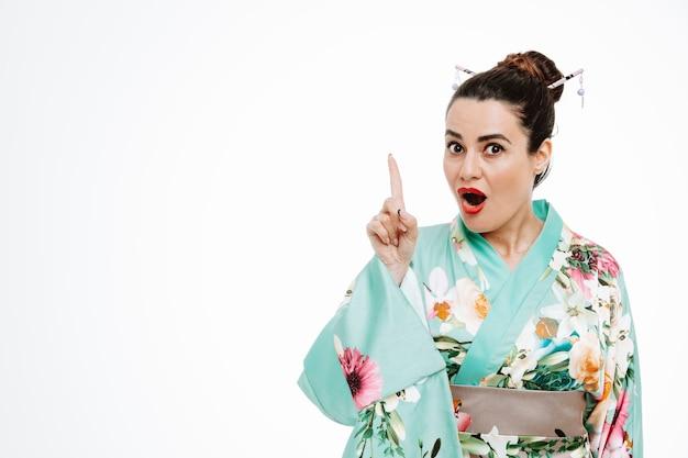 일본 전통 기모노를 입은 여성이 흰색에 대한 새로운 아이디어를 가지고 검지 손가락으로 가리키며 놀랐습니다.
