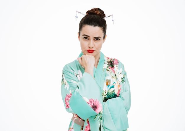 白で彼女のあごに手をつないで懐疑的な表現を持つ伝統的な日本の着物の女性