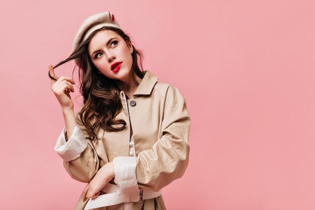 トレンチコートとベレー帽をかぶった女性は、思慮深く見上げ、唇を噛み、髪を指に巻き付けます。