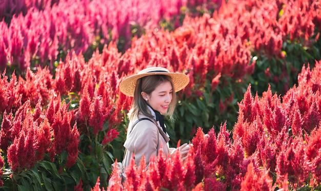 赤い花畑のトレンチコートと麦わら帽子の女性。