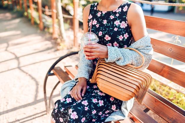 公園で座っているとスムージーを飲むトレンディなカーディガンの女性