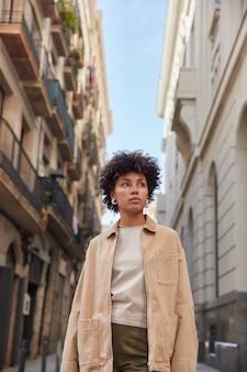 トレンディな服装の女性が古代の建物の近くの通りを散歩し、周りを見回し、宣伝エリアが美しい建築物を通過する都市を散歩する自由な時間を楽しんでいます