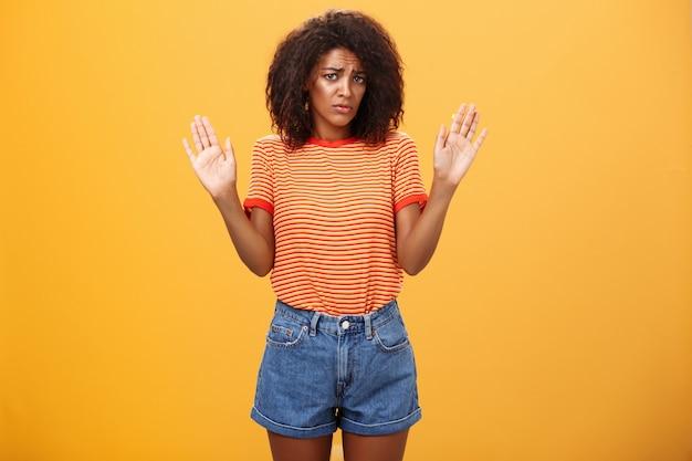 Женщина в модной полосатой футболке и шортах поднимает руки, сдаваясь.