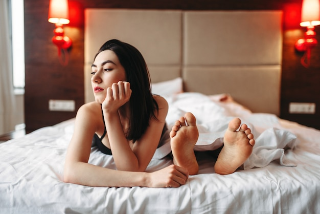 男性の足に対してベッドで横になっている下着の女性。ベッドの中で親密なゲーム。セクシーな愛のカップル、寝室の親密さ