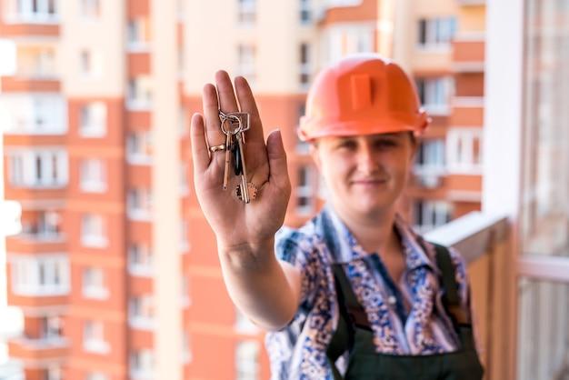 새 아파트에서 열쇠를 보여주는 유니폼과 헬멧에 여자