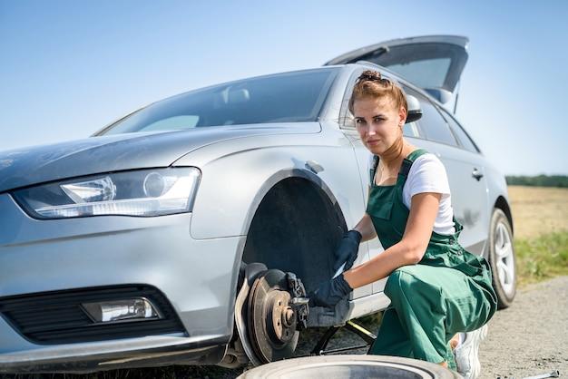 자동차 브레이크 유지 보수를 위해 일하는 제복을 입은 여자. 자동차 수리. 안전 작업