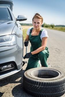 자동차 브레이크 유지 보수를 위해 일하는 제복을 입은 여자. 차 수리. 안전 작업