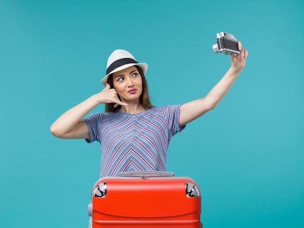 青で写真を撮るカメラを持って休暇中の女性