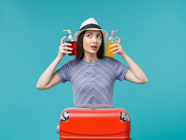 青に新鮮な飲み物を持って休暇中の女性