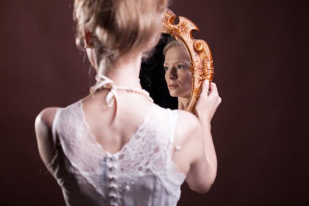 Mirrod를 손에 들고 빅토리아 드레스에 여자입니다. 풍부하고 빈티지합니다. 럭셔리와 우아함. 스튜디오 사진
