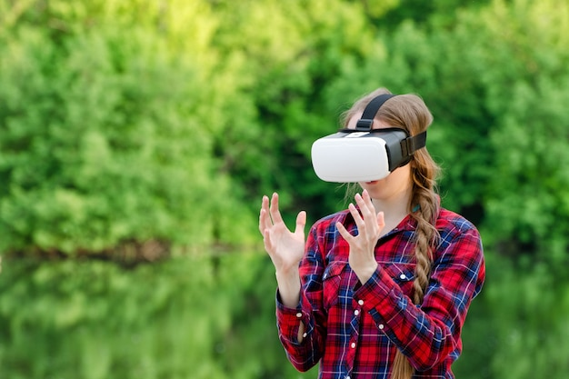 バーチャルリアリティメガネの女性は、緑を背景に、彼女の前に手を握っています