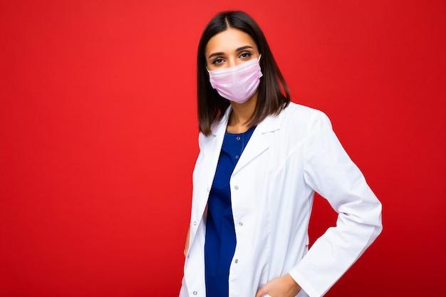 コロナウイルスと背景に分離された白い医療コートに対する顔のウイルス保護マスクの女性。
