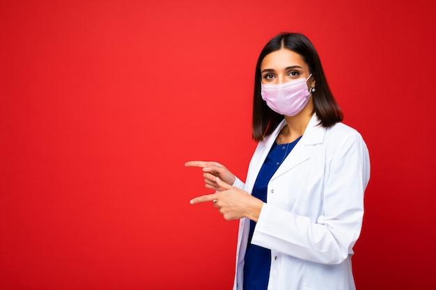 コロナウイルスと白い医療コートに対する顔のウイルス保護マスクの女性