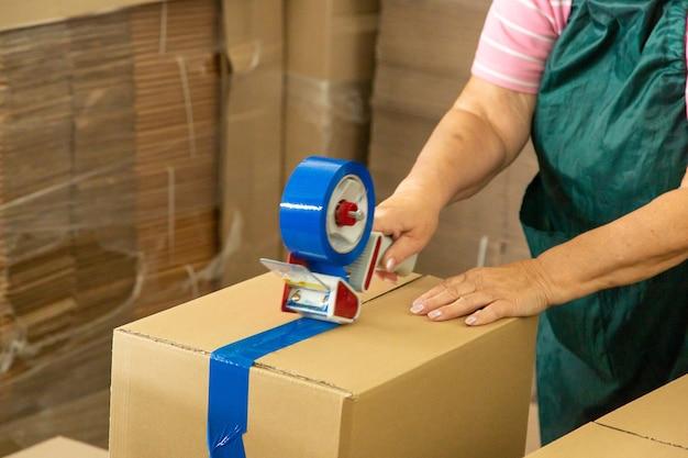창고 작업자 유니폼을 입은 여성이 배달을 위해 판지 상자를 포장합니다.