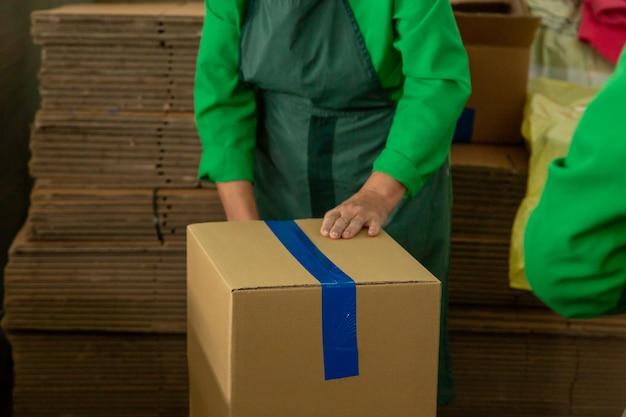Женщина в униформе складского работника упаковывая картонную коробку для доставки.